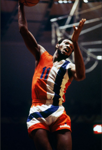 Here we have one of the most unusual uniforms in NBA history! The super-prominent striping makes it easy to miss the most radical aspect of the design, which is that neither the team name nor the city name appears on the jersey for the Washington Bullets.